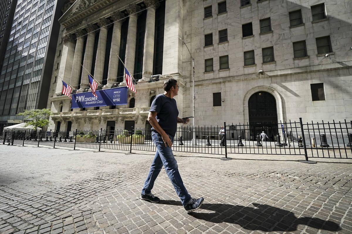 A pedestrian pass the New York Stock Exchange, Friday, Oct. 2, 2020, in New York. Stocks aroun ...