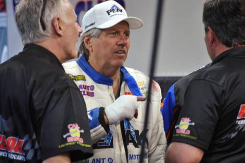 John Force talks to crew members after his Funny Car blew an engine and destroyed the body of h ...
