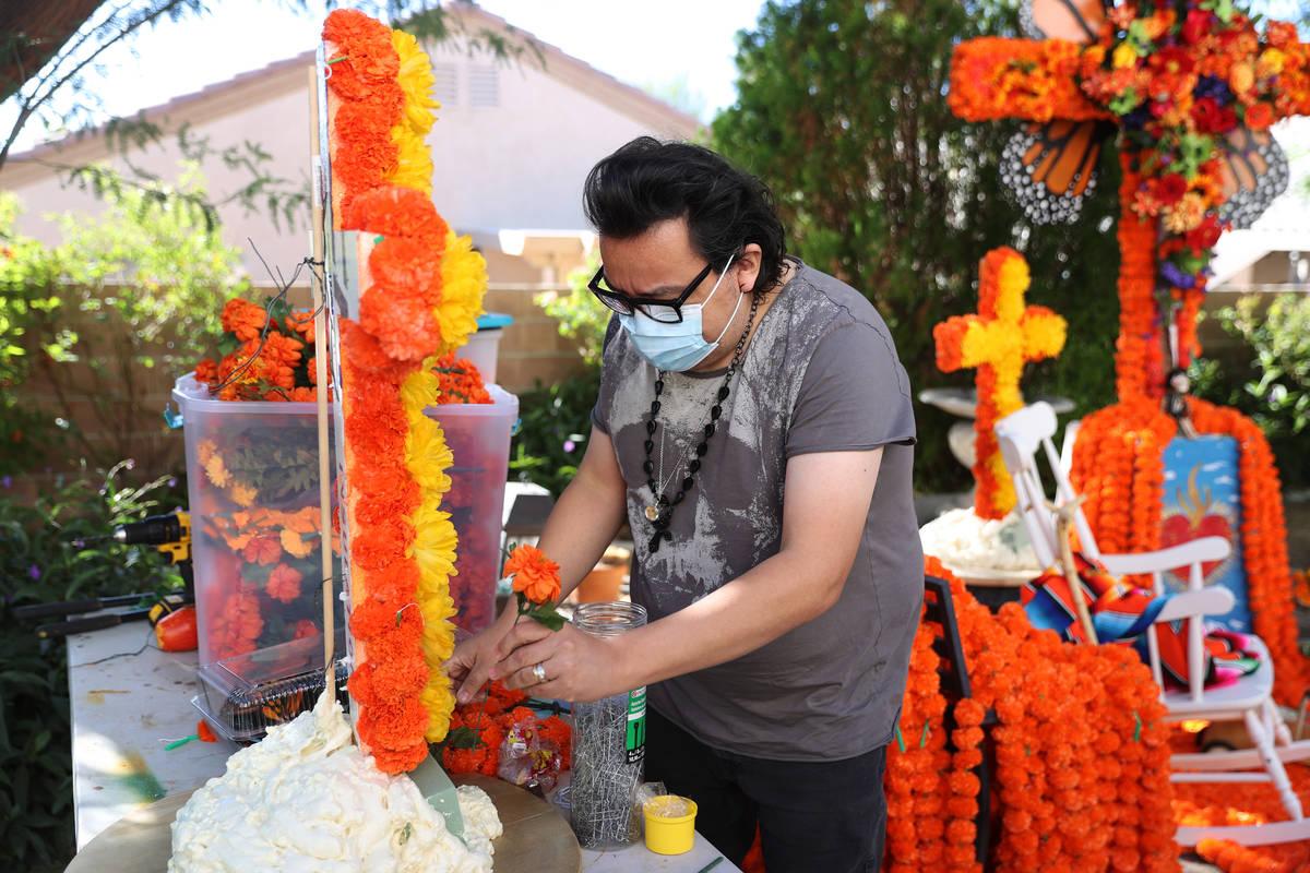 Isaias Urrabazo works on his Dia de los Muertos altar at his home in Las Vegas, Saturday, Oct. ...