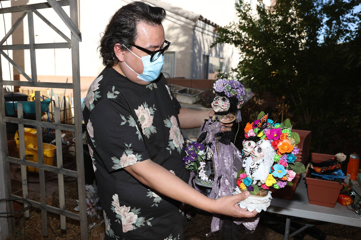 Artist Isaias Urrabazo shows dolls he created inspired by Dia de los Muertos, at his home in La ...