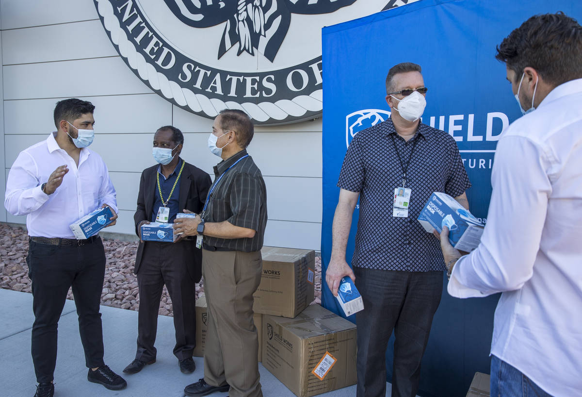 The owners of Shield Works gather with VA Hospital personnel to donate 100,000 masks to the fac ...