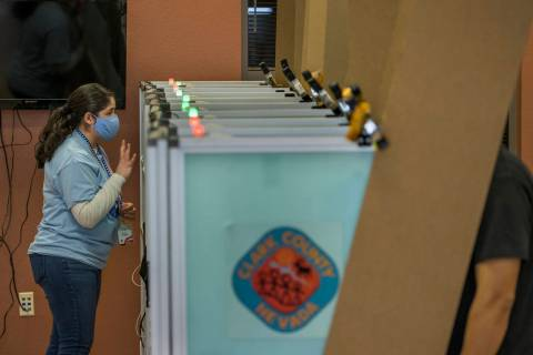 An elections worker gives instructions to a voter while in a booth with lights above showing th ...