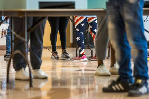A volunteer in flag attire assists a voter at a voting machine at the Doolittle Community Cente ...