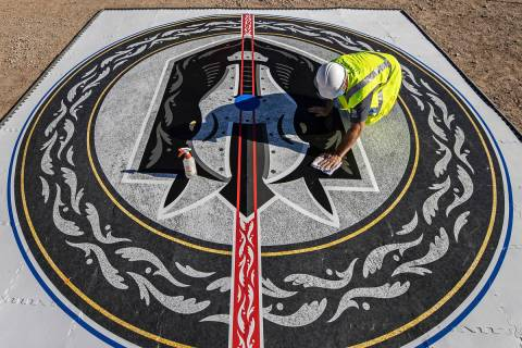 Construction workers put the finishing touches on the Henderson Silver Knights logo during a co ...