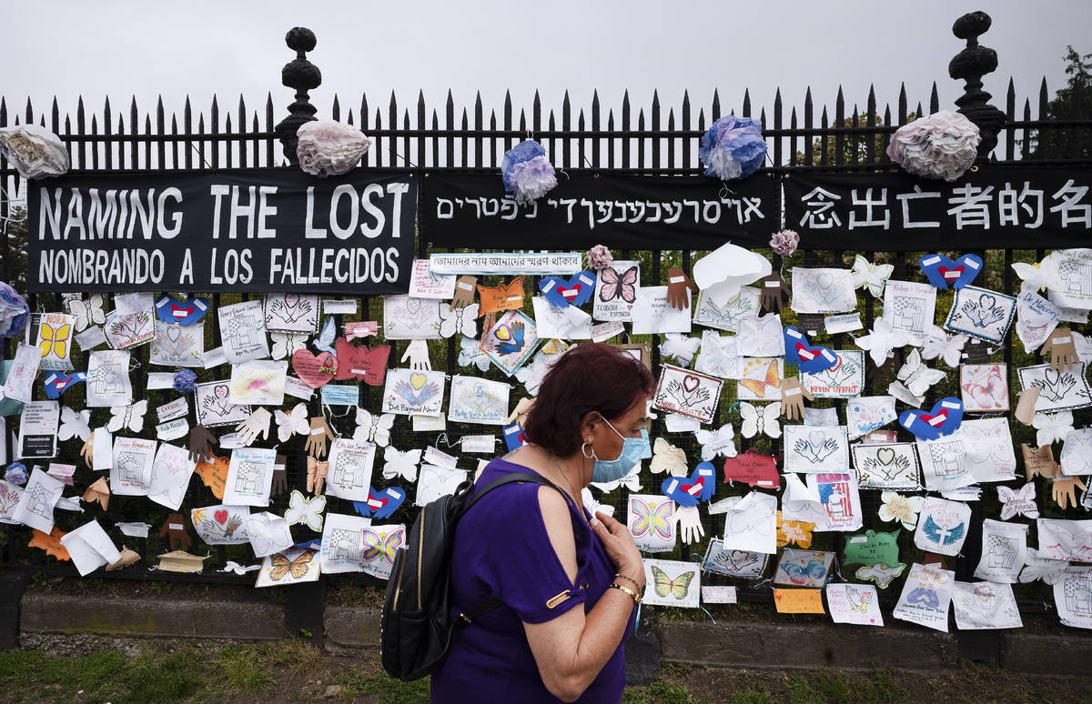 A woman passes a fence outside Brooklyn's Green-Wood Cemetery adorned with tributes to victims ...