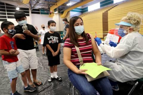 Melanie Navarrete of Las Vegas gets a flu vaccine from Lynda McCloskey as her children, from le ...