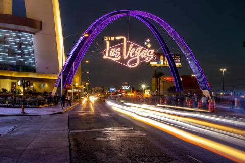 Cars stream down Las Vegas Boulevard as the downtown gateway arches are fully illuminated for t ...