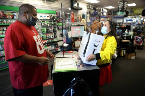Chris Brown picks up a Play Station 5 console from store manager Jane Esposo at GameStop, 9975 ...