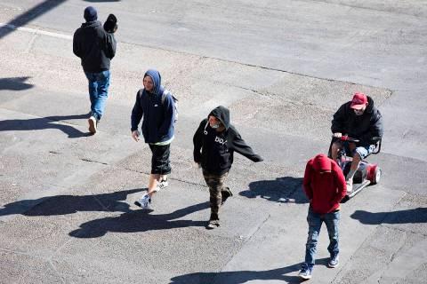 Visitors bundled in sweatshirts and jackets cross Las Vegas Boulevard at Fremont Street in Down ...