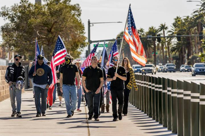 A small group walks south of the Tropicana during a Veterans Day march to peacefully protest Go ...