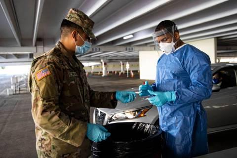 Nevada National Guard specialists Jonathan Macias, left, and Demetrie Barnett prepare to store ...