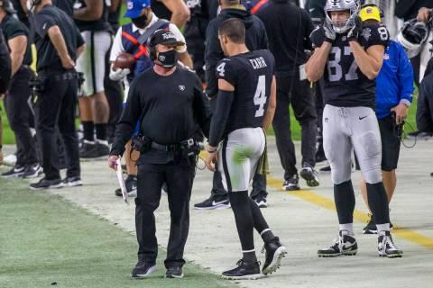 Las Vegas Raiders head coach Jon Gruden, left, interacts with quarterback Derek Carr (4) on the ...