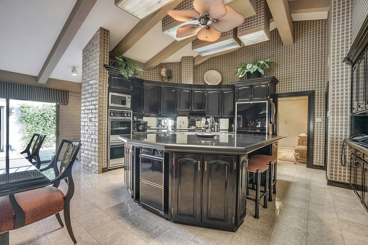 Rich black lacquer cabinetry and black granite counters create a sophisticated modern aesthetic ...