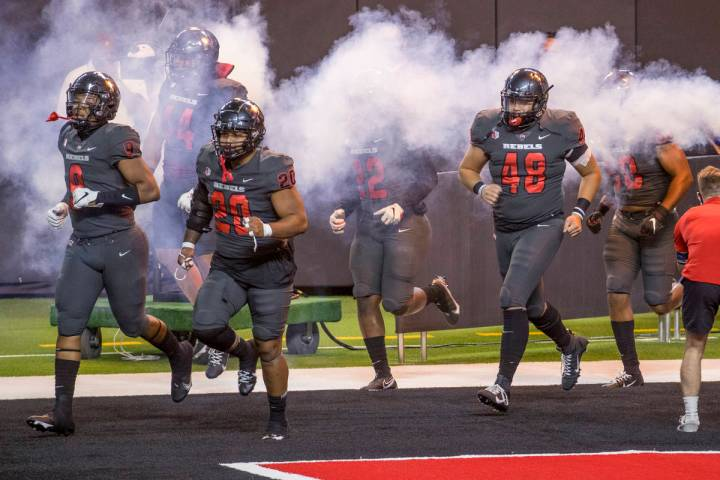 UNLV Rebels players take the field to face the Nevada Wolf Pack before the first half of their ...