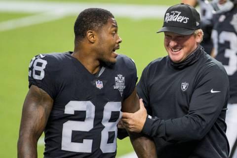 Las Vegas Raiders running back Josh Jacobs (28, left) jokes around with head coach Jon Gruden d ...