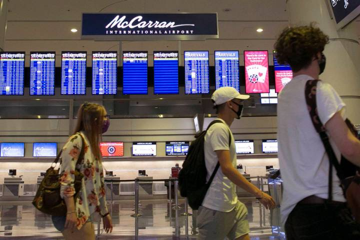 In this June 24, 2020, file photo, travelers walk past McCarran International Airport sign in L ...