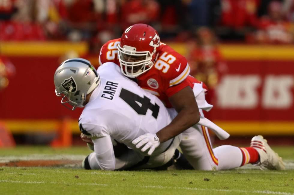 Oakland Raiders quarterback Derek Carr (4) is sacked by Kansas City Chiefs defensive end Chris ...