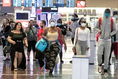 Arriving passengers head toward a baggage claim area at McCarran International Airport on Thurs ...
