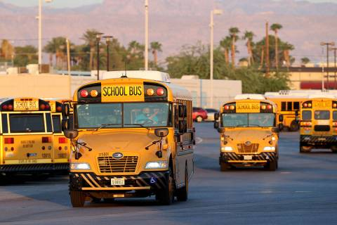 Drivers head out of the Clark County School District Arville Bus Yard in Las Vegas on the first ...