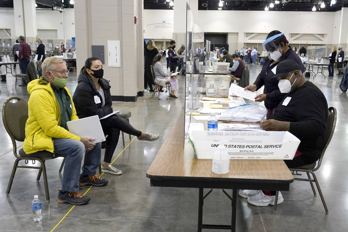 Election workers, right, verify ballots as recount observers, left, watch during a Milwaukee ha ...