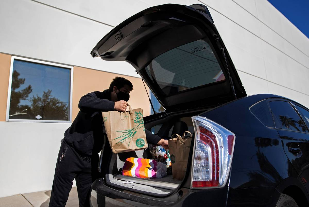 Tristan Sanchez delivers bags of donated food to a vehicle during a food drive hosted by Nectar ...