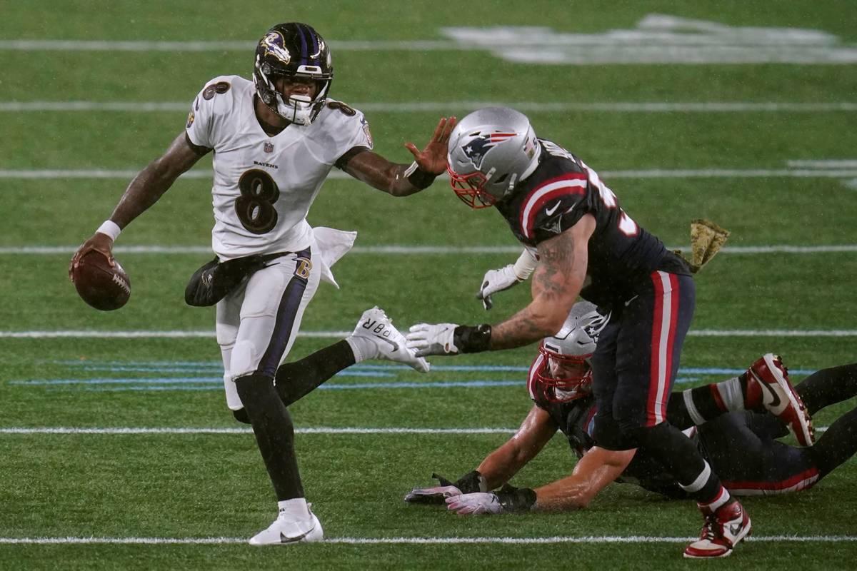Baltimore Ravens quarterback Lamar Jackson, left, tries to elude New England Patriots defensive ...