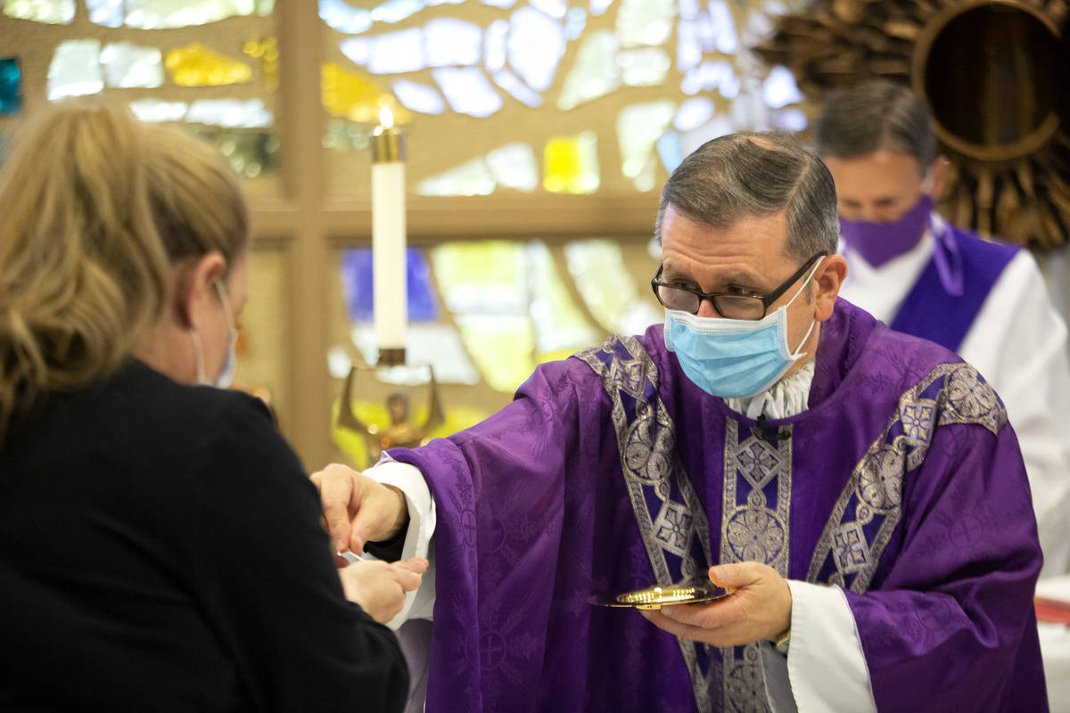 Jennifer Berelowitz, receives communion from Msgr. Gregory Gordon during a virtual Mass at the ...