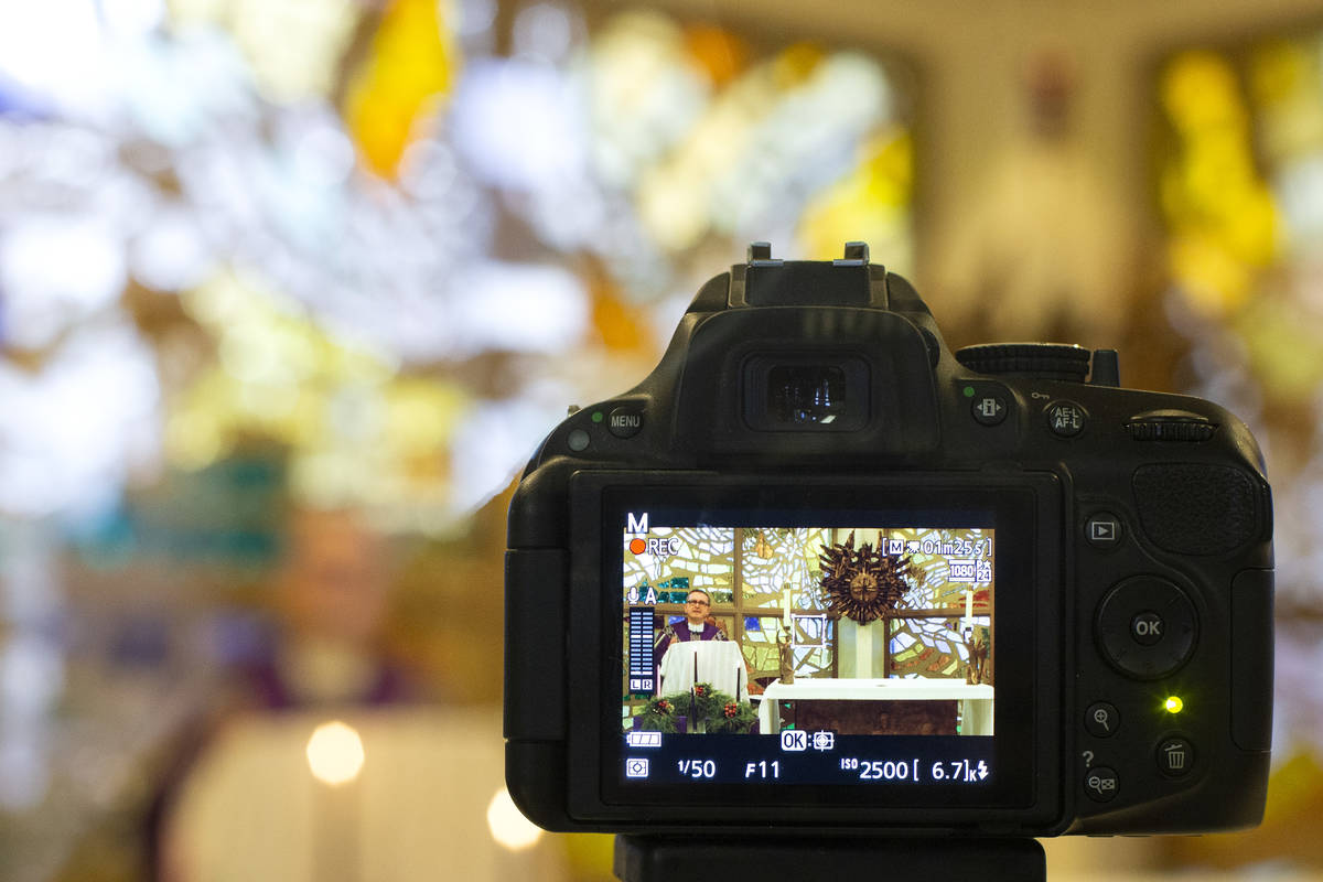 A camera records Msgr. Gregory Gordon giving a virtual Mass at the The Roman Catholic Diocese o ...