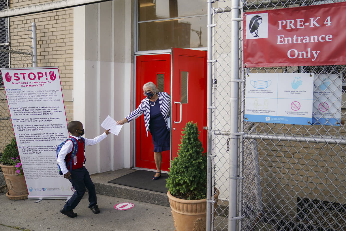 FILE - In this Sept. 9, 2020, file photo, a student wears a protective masks as they arrive for ...