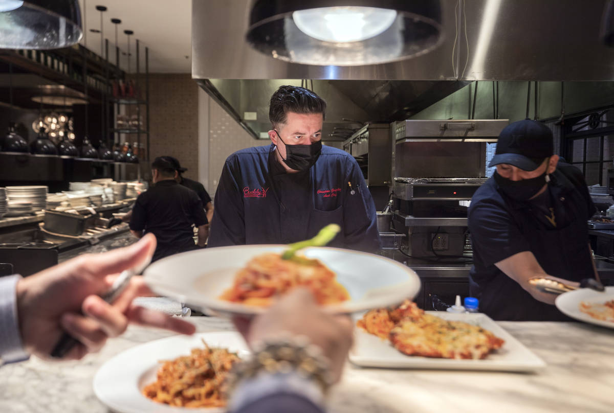 Executive sous chef Christian Gonzalez-Borda, center, oversees dishes going out to be served at ...