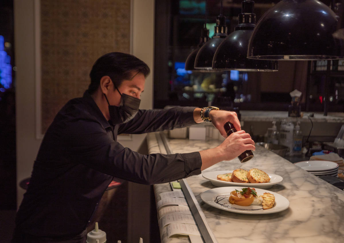 Server Alex Romero puts the final touches on dishes at Buddy V's Ristorante at The Venetian the ...