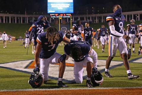 Virginia players take a knee after an NCAA college football game against Abilene Christian, Sat ...