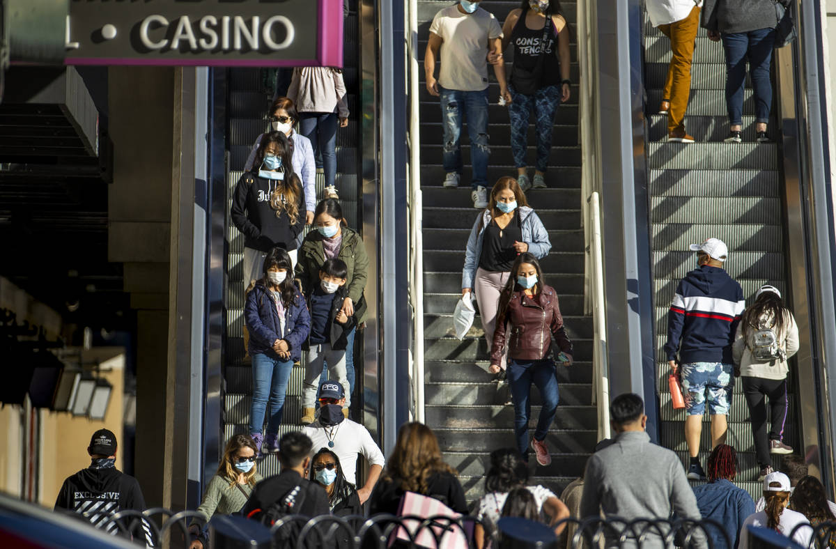 A crowd moves about outside of The Cromwell from a pedestrian bridge along the Las Vegas Strip ...