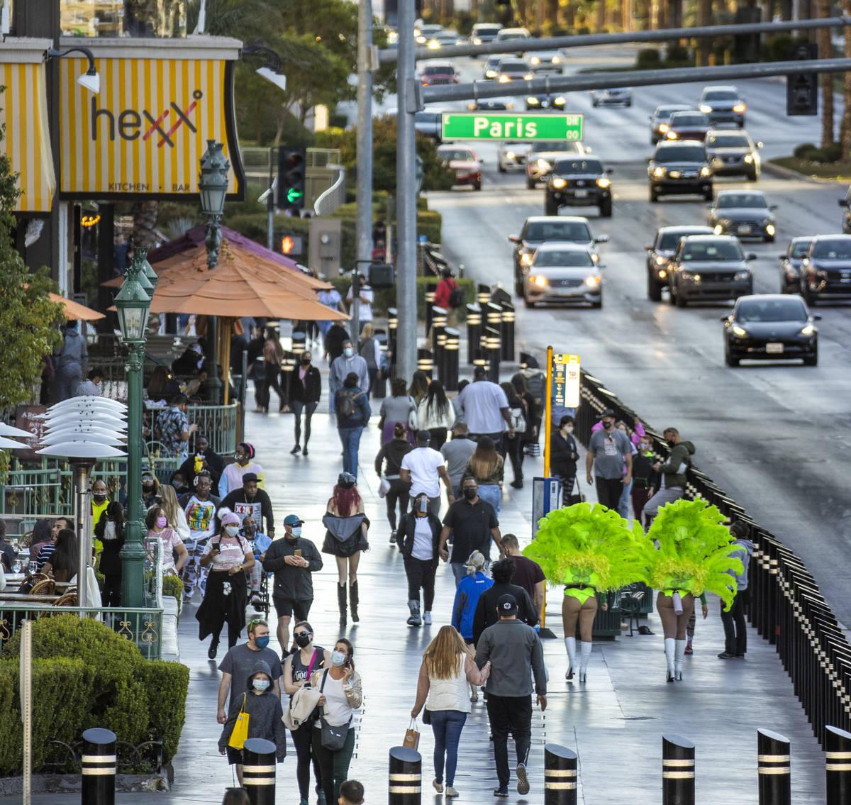 Pedestrians crowd the sidewalk adjacent to the Paris Las Vegas along the Las Vegas Strip on Tue ...