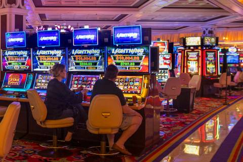 Slot players at the Wynn Las Vegas sit side by side while Gov. Steve Sisolak tours the casino t ...