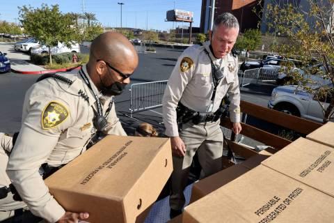 Las Vegas police officers S. Florial, left, and T. Howell load turkeys at Metropolitan Police D ...