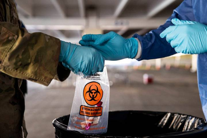 Nevada National Guard specialists Jonathan Macias, left, and Demetrie Barnett store a test tube ...