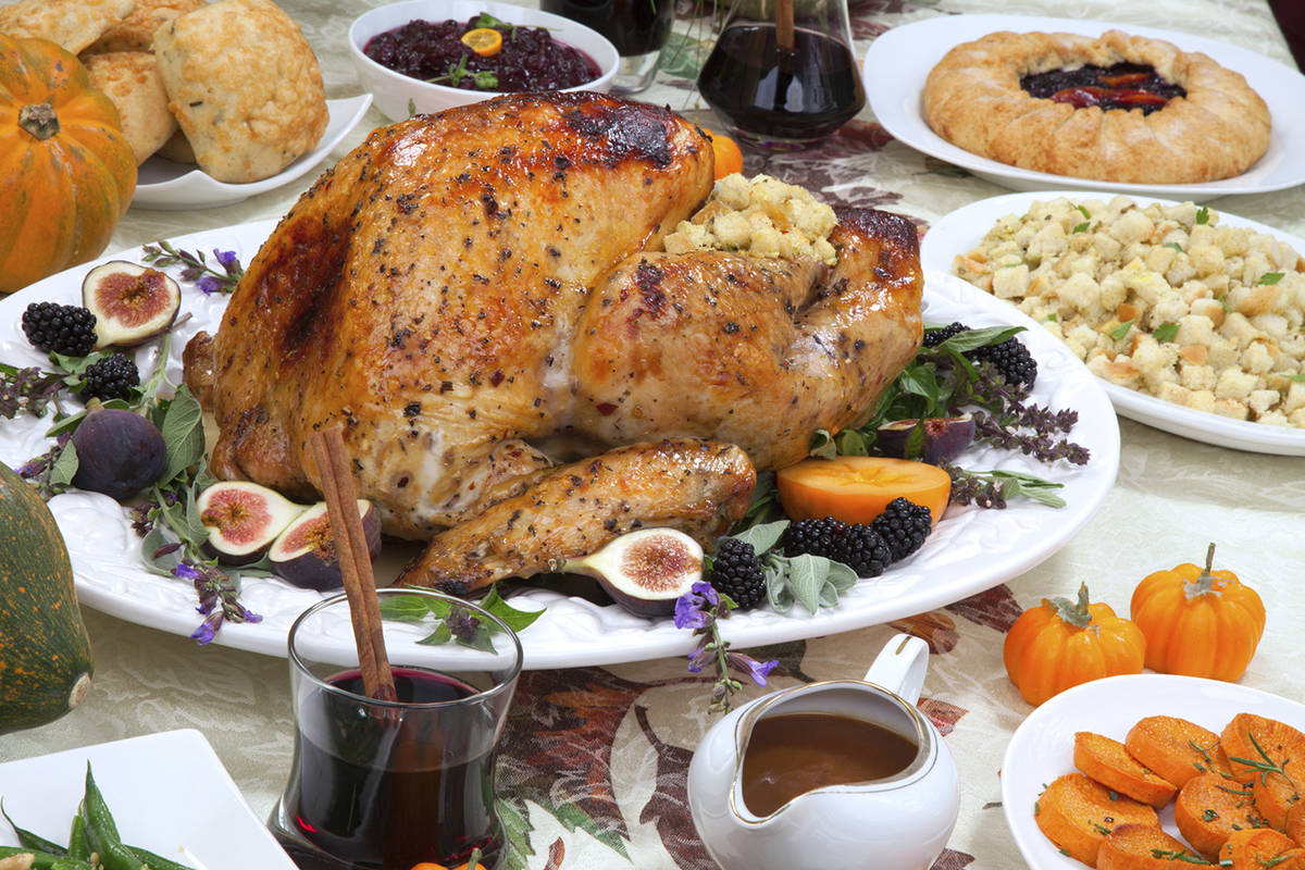 Dinner table with roasted Thanksgiving turkey is ready to feast. Turkey is garnished with fresh ...