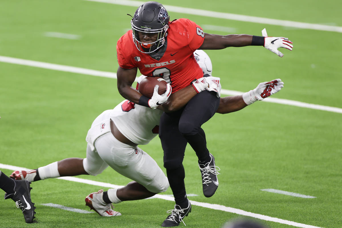 UNLV Rebels running back Charles Williams (8) is tackled by Fresno State Bulldogs linebacker Ma ...