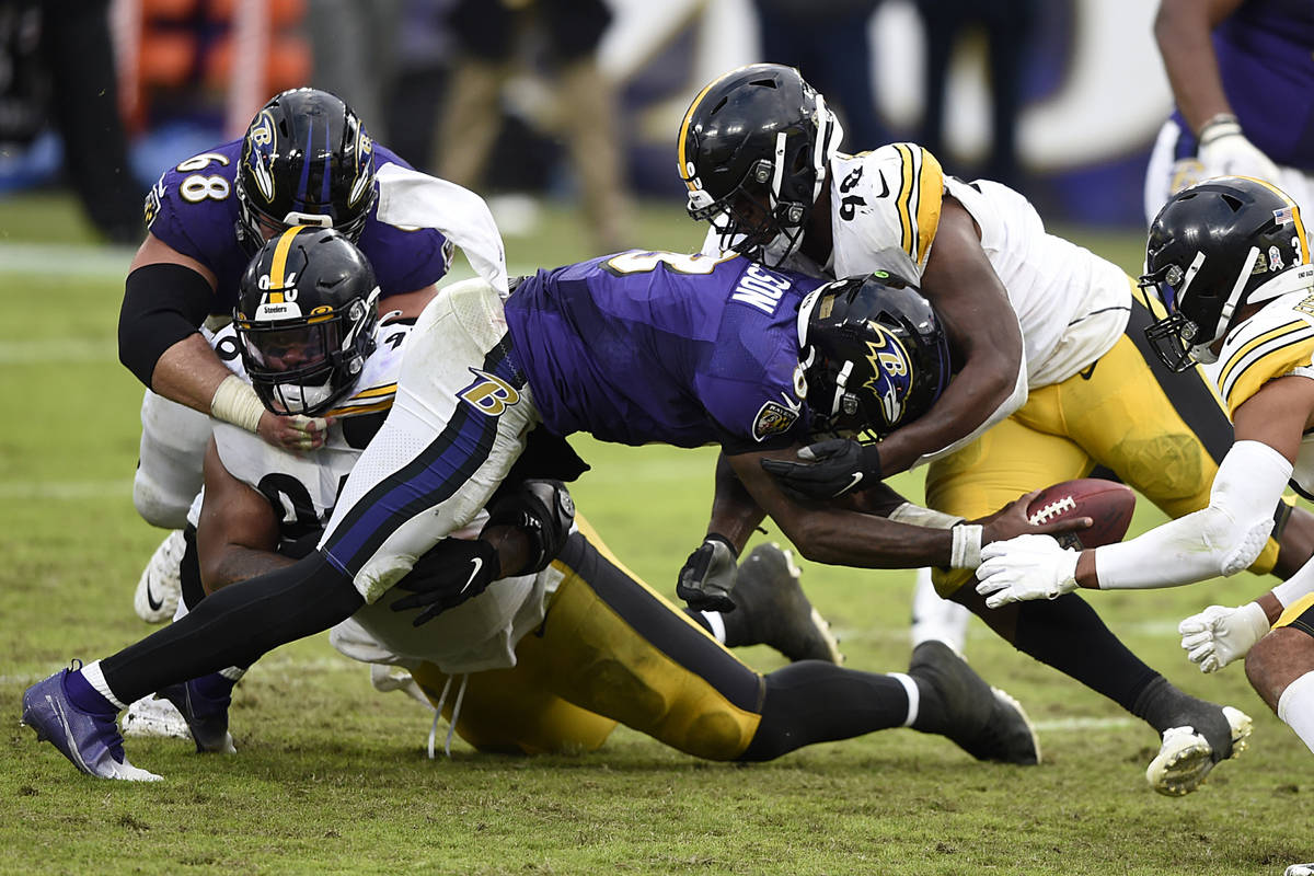Baltimore Ravens quarterback Lamar Jackson is tackled by Pittsburgh Steelers Isaiah Buggs durin ...