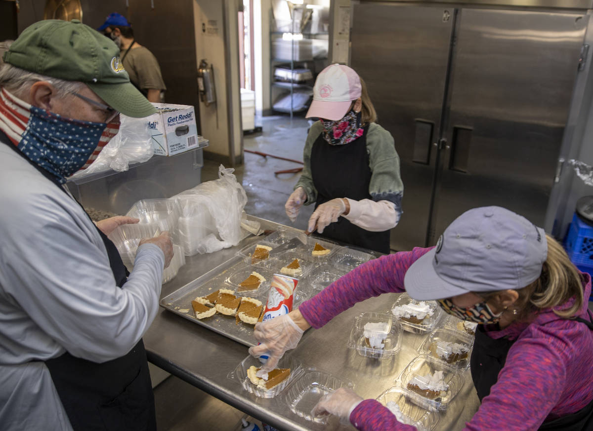 Volunteers serve up pie as part of a Thanksgiving meal at the Las Vegas Rescue Mission with foo ...