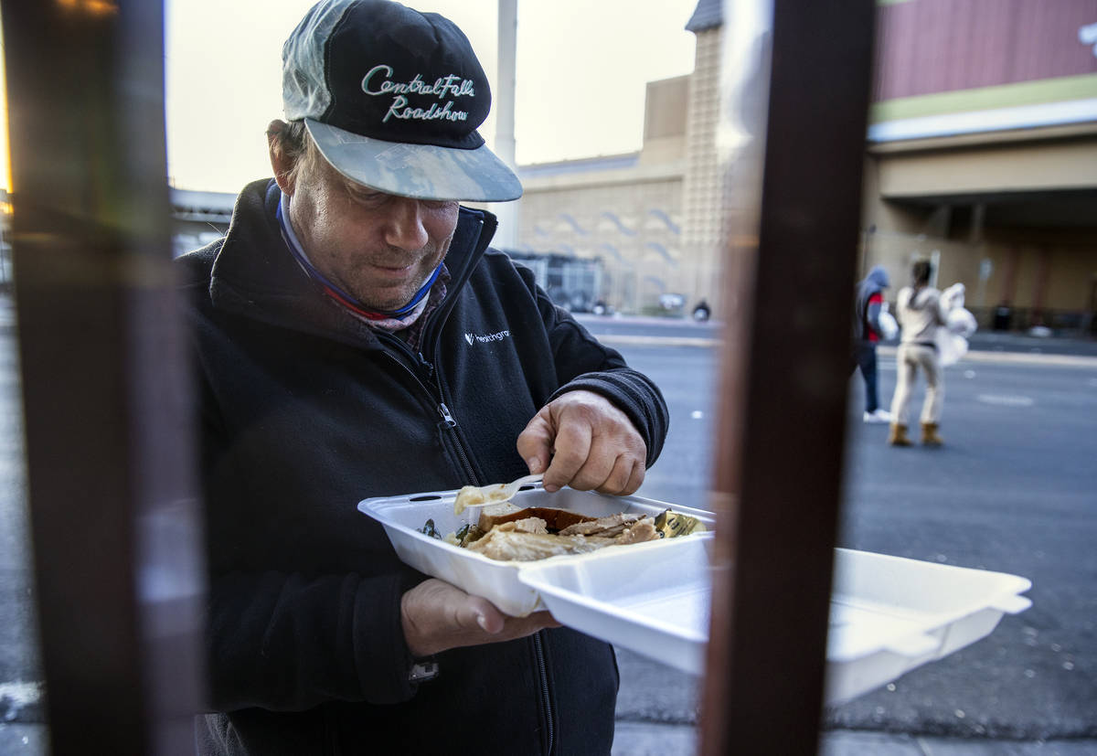 Phil Harnischfeger enjoys a prepared Thanksgiving meal outside the Las Vegas Rescue Mission wit ...
