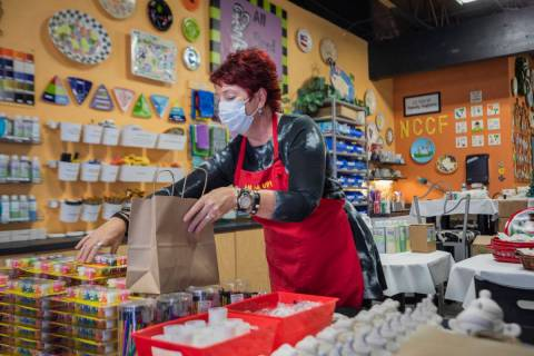Co-founder of All Fired Up, Gail Schomisch, packs a holiday pottery to-go kit in the pottery st ...