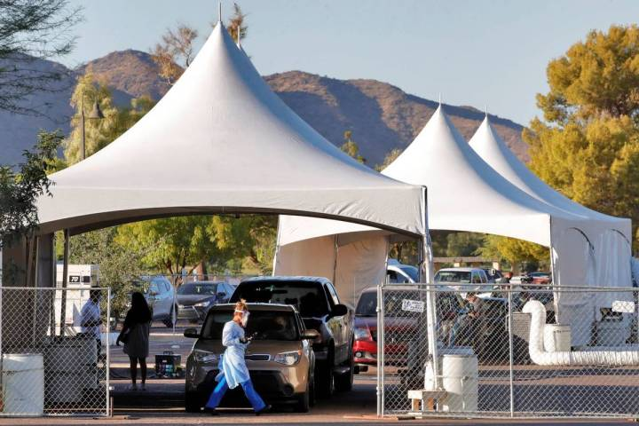 People wait in line to be tested for COVID-19 at Cesar Chavez City Park in Phoenix in July 2020 ...