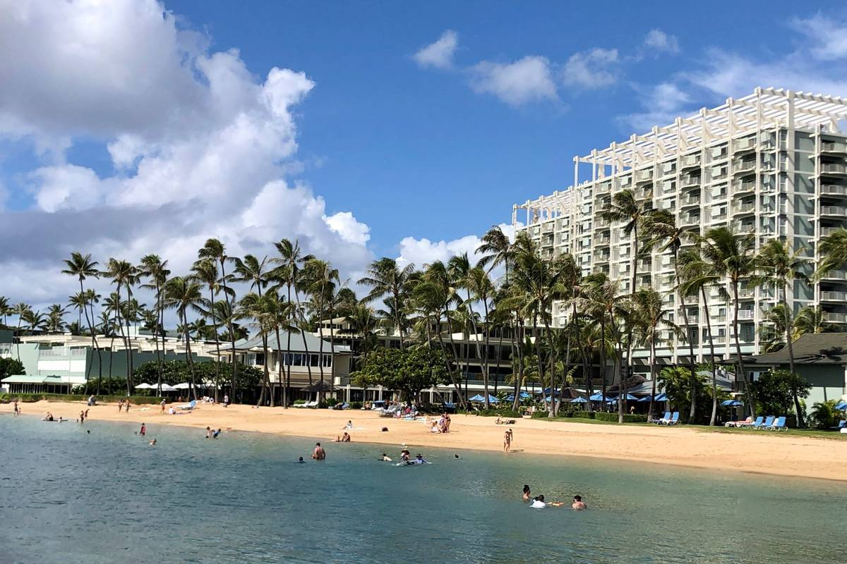People are seen on the beach and in the water in front of the Kahala Hotel & Resort in Honolulu ...