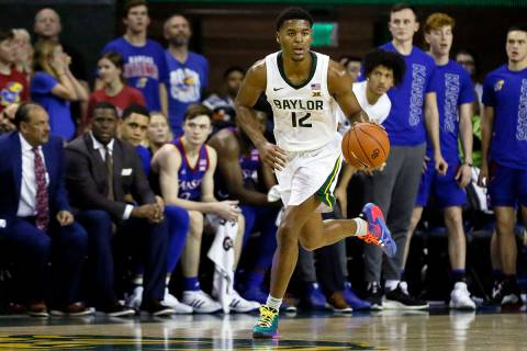 Baylor guard Jared Butler dribbles up court against Kansas during an NCAA college basketball ga ...