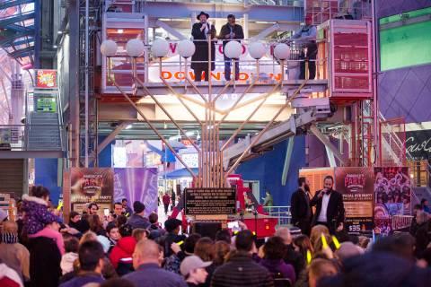Rabbi Shea Harlig lights the menorah for the start of Hanukkah as David Dahan recites blessings ...