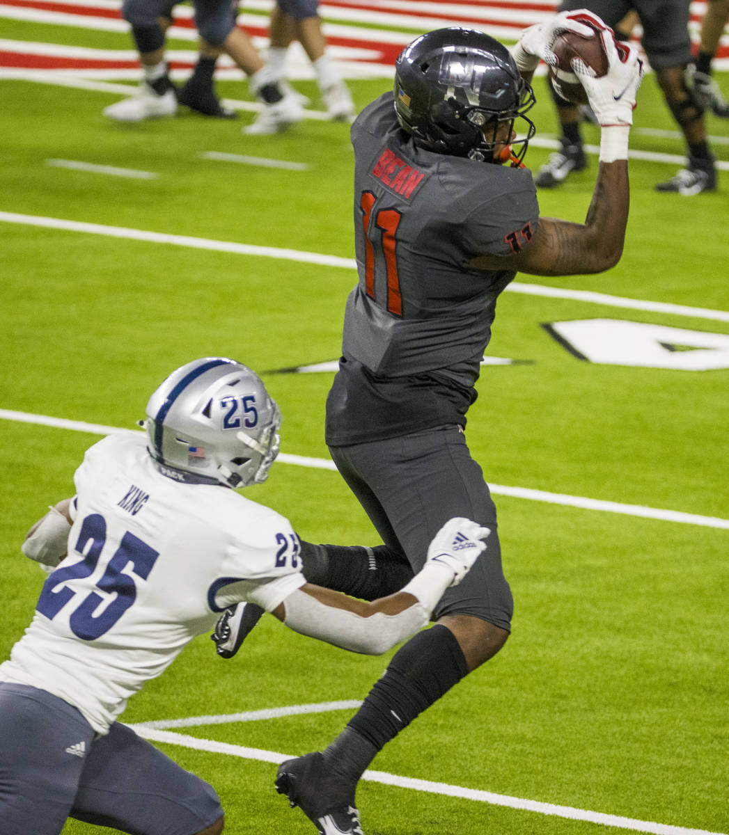 UNLV Rebels tight end Noah Bean (11, top) secures a pass above Nevada Wolf Pack defensive back ...