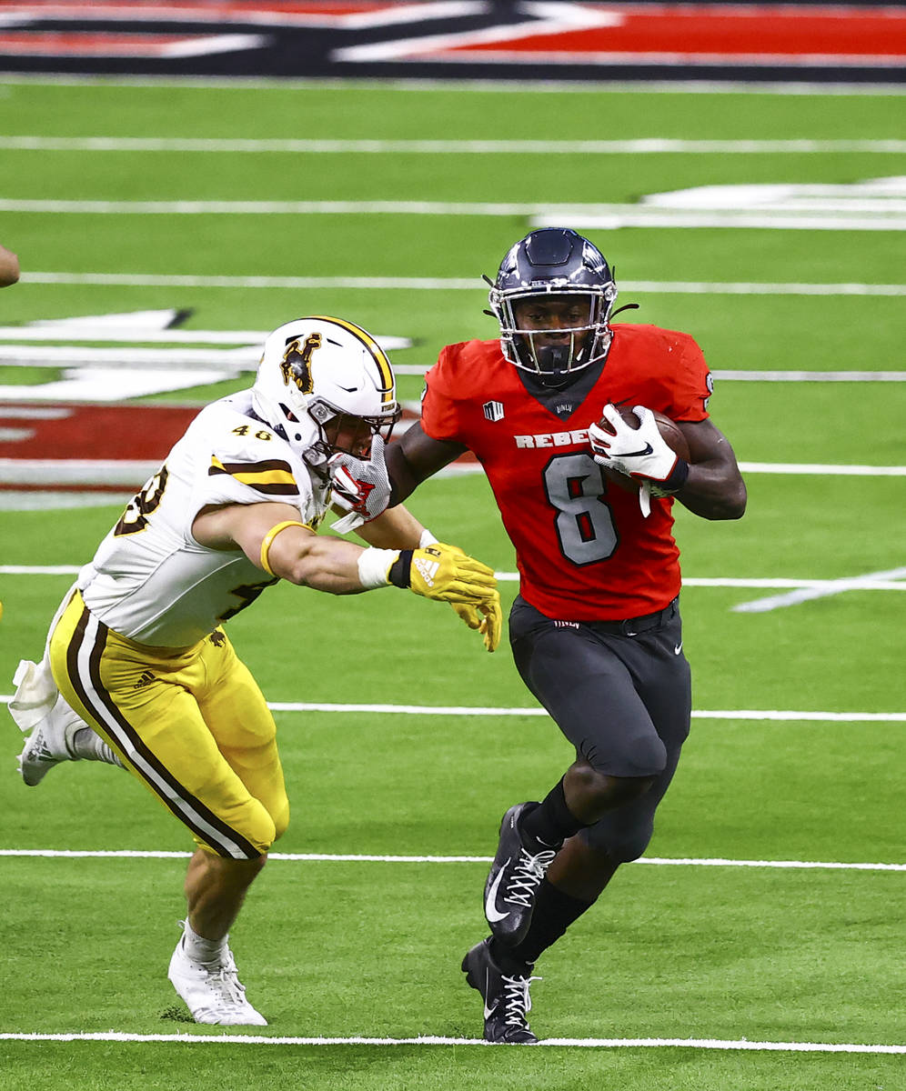 UNLV Rebels running back Charles Williams (8) runs the ball under pressure from Wyoming Cowboys ...