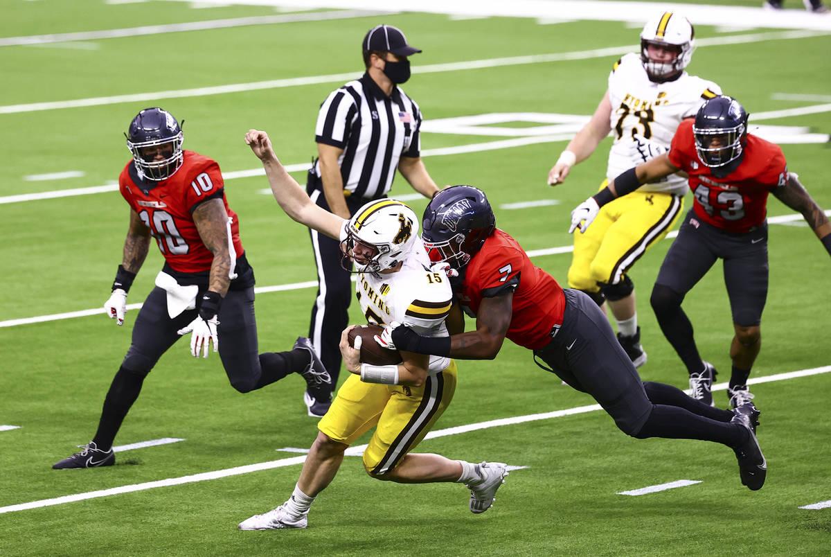 UNLV Rebels defensive lineman Adam Plant Jr. (7) tackles Wyoming Cowboys quarterback Levi Willi ...